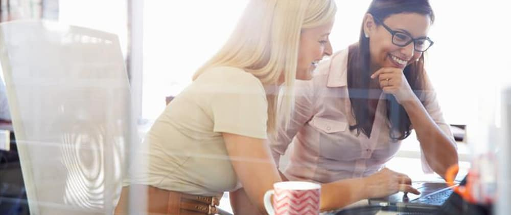 Women sitting together looking at laptop